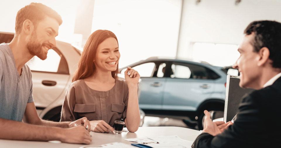 Junges Paar beim Kauf eines Neuwagens
